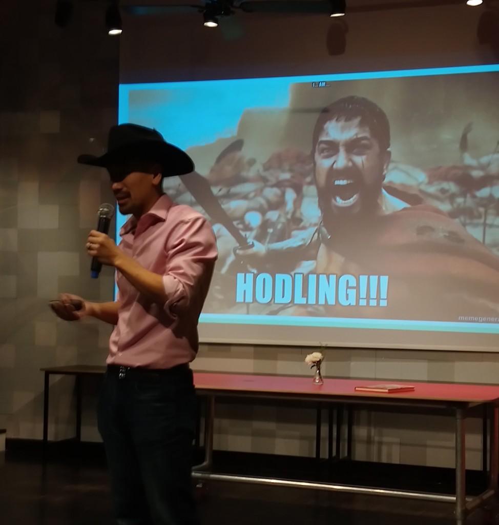 ג'ימי סונג, יזם ביטקויון ומפתח בלוקצ'יין בעל שם עולמי, בהרצאה בתל אביב. הפוסטר מאחוריו מעודד אנשים לעשות HODL, כלומר, להחזיק את הביטקוין שלהם בארנק ולא לבזבז אותו. צילום: מתן שפירא
