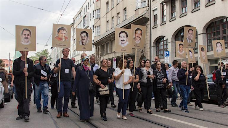 משפחות הקורבנות של המחתרת הנאצית עם תמונות הנרצחים, בהפגנה נגד סיום החקירה, אוגוסט 2018 (מקור: טוויטר)