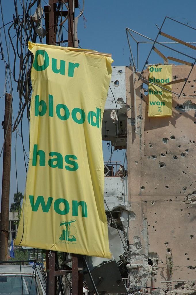 """כרזות של חיזבאללה בדרום לבנון לאחר מלחמת לבנון, 2006. דגל חיזבאללה. """"הארגון הפך לאחד הגורמים העיקריים שמרוויחים מהשיטה ומגנים עליה"""". צילום: Julien Harneis, CC BY-SA 2.0"""